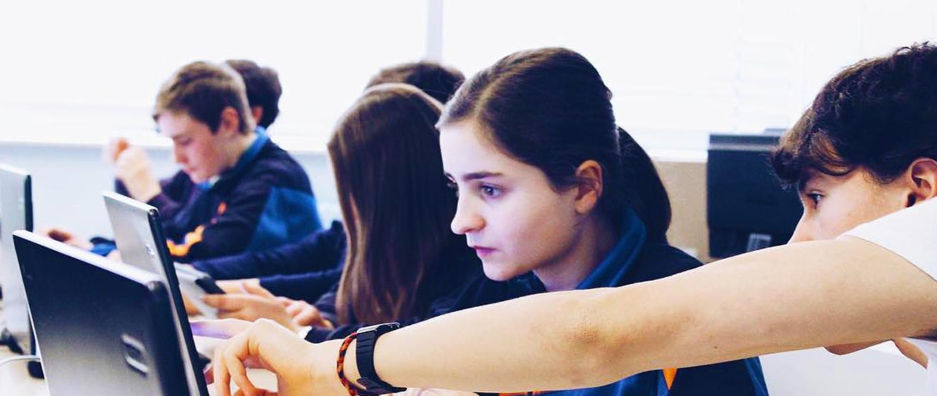 niños en clase con ordenadores portatiles