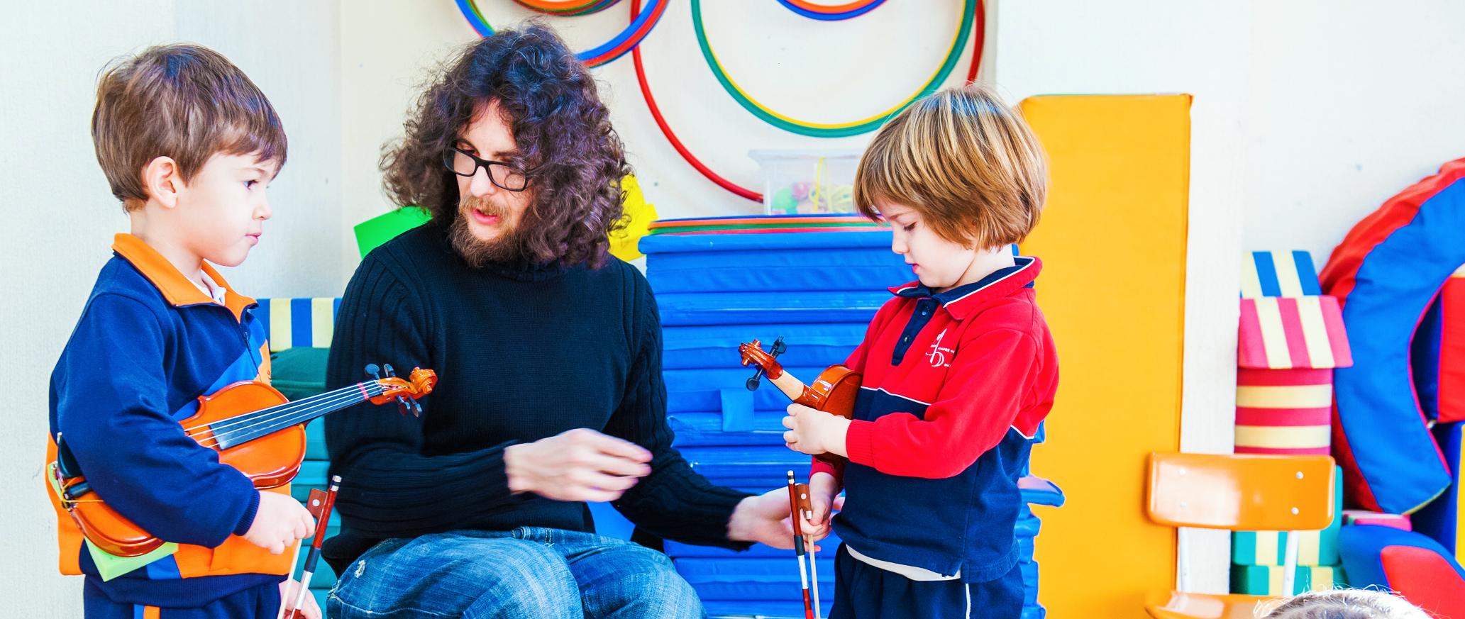 niños con violines y profesor de música